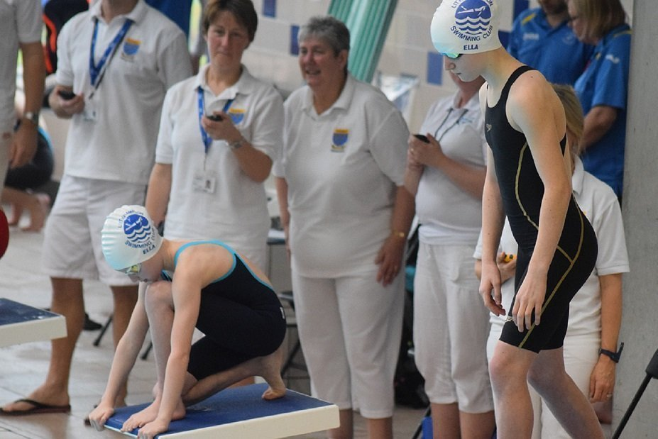 2 LSC swimmers on blocks with officials around
